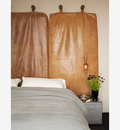 Ashe + Leandro - Leather cushion wall hanging for headboard in this bedroom