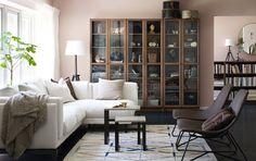 BILLY Bücherregale in braunem Eschenfurnier mit OXBERG Vitrinentüren mit braunem Eschenfurnier in einem modern eingerichteten Wohnzimmer