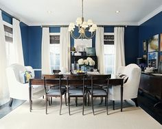 color: Benjamin Moore Champion Cobalt    Ashley Putman - Gorgeous blue & brown dining room design with bold blue walls paint color, chair rail, wood turned leg dining table, wood, dining chairs with blue striped ticking cushions, seagrass rug, slipcovered wingback captain chairs, brass brass chandelier, white cotton drapes, bamboo roman shades, white drapes and art gallery.