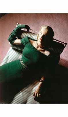 Model on striped couch wearing a deep green wide-neck knit dress by Hattie Carnegie, jewelry from Seaman Schepps July 1943
