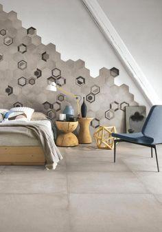 Zona notte con decorazione di piastrelle esagonali al posto della testata del letto.