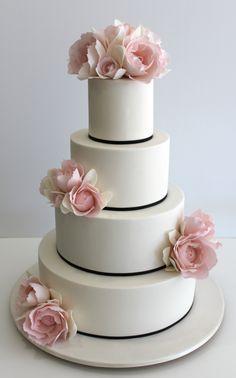White wedding cake with black ribbon border and flowers
