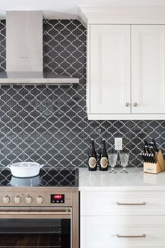 Black arabesque backsplash tiles are a major key feature in this white kitchen against white and stainless steel accents.