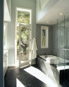 BATHROOM REMODELING MODERN DESIGN: Natural Light & An Outdoor View This modern bathroom design includes large windows that bring in plenty of natural light to brighten up the room and a glass door that leads out to the backyard.
