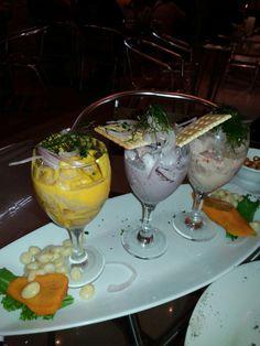 """Un trio infaltable en la comida marina peruana, tres copas de: """"Tiradito"""" de pescado, pulpo al olivo y cebiche tradicional. A base de limón con su ajicito. También con """"choclito"""" y Camote (papa dulce) glaceado. Buenazo."""