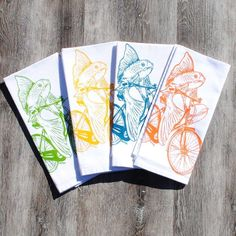 Cotton Table Napkins Set of 4 Screen Printed Fish on a Bike. Set of four table napkins that are washable and reusable. These are bright white cotton napkins featuring images of a fish on a bicycle. I personally hand draw all of my designs and hand pull all of my screen print images. The printed napkins set is eco-friendly napkins premium quality 100% cotton. They are nice and thick and will stand up to everyday wear. I use high quality water based inks that are earth friendly and...