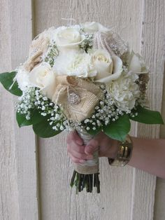 This charming hand held Bouquet featuring cream Vendela roses, white Carnations, and Gypsophilia, and a touch of lemon leaf. Stem wrapped with burlap and an overlay of ivory lace featuring hand made burlap flowers with bling.