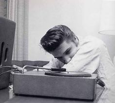 Elvis Presley listening to a record
