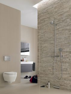 A wall-mounted toilet helps this spa-inspired bathroom with a stone accent wall feel more open. Small Bathroom Tiles, Modern Master Bathroom, Bathroom Layout, Modern Bathroom Design, Bathroom Designs, Stone Accent Walls, Stone Walls, Spa Inspired Bathroom, Wall Mounted Toilet