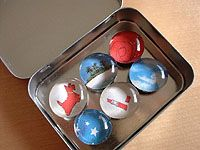 make Magnets  ~ buy 1/2″ and 3/4″ round (strong) magnets ~  1/2″ and 3/4″ clear flat glass marbles  ~  silicon sealer made by Krazy Glue. All of the pictures were cut out of  magazines.   Great to package Magnets in Altoid-sized tins.