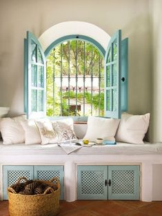 Window nook painted a fun turquoise and decorated with pillows to compliment