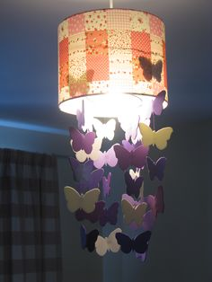 Butterfly Chandelier. I saw the idea on Pinterest (check Cool Bedroom Ideas board) but I didn't have the nifty cutting machine they used so I cut them out by hand using thin foam sheets in a variety of purples and white. The white butterflies appear yellow in the light and they're all strung from fishing wire tied to a loop of garden wire. I also changed the bulb to a low energy bulb to keep the heat down so the foam wouldn't melt inside. The lampshade is from B.