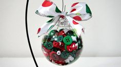"""What a cute ornament for Christmas decorating! A 3"""" diameter glass clear ball filled with red, green and white buttons and beads. Finished with a 1"""" white, red and green polka dot wired ribbon with a silver edge."""