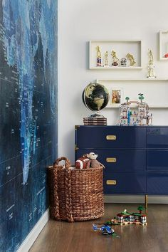 Contemporary boy& room features a navy blue lacquered campaign dresser placed beneath staggered white box shelves mounted on a white wall as a woven toy basket sits in front of a wall covered in a blue world map mural.