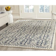 Safavieh's Cambridge Collection is the ultimate illustration of traditional elegance. This navy blue hand-tufted wool rug brings a Moroccan inspired bold geometric pattern to any living space.