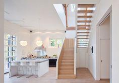 Un grosso bancone con tre sgabelli alti da un lato: una soluzione flessibile che permette di ottenere un piano d'appoggio per colazione e pranzi veloci in cucina. È la soluzione scelta dagli studi Zecc Architects e BYTR Architects per un'ex stalla con fienile ristrutturata nei pressi di Breukelen, in Olanda.