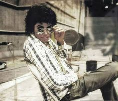Michael Jackson in a plaid shirt lowers his glasses towards the camera.