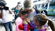 Courtney Gelinas, left, is hugged by her mother Kim Lariviere, center, after being reunited with her stuffed bear Rufus, at the Fort Lauderdale-Hollywood International Airport on Tuesday.