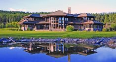 montana log homes | Long winding driveway leading up to the main entrance of elegant stone