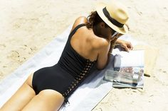 Woman at the beach in black lace-up one shoulder one piece swimsuit with sunhat.