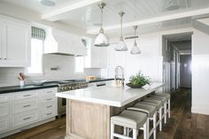 Beach style kitchen.  Dark outer countertops.  Stained island. White island countertops.