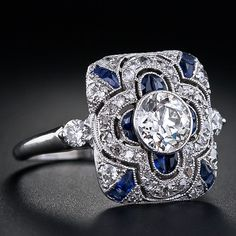 Art Deco diamond dinner ring in platinum, with 0.80ct European cut center diamond bezel set with antique cut diamonds and synthetic sapphires.