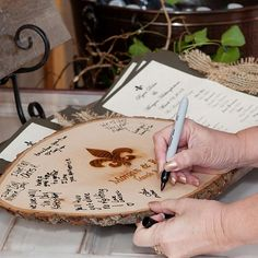 A slice of fresh wood engraved with Morgan and Ryan's names was put out at the ceremony for guests to leave a loving message for them to remember their wedding day which can easily be displayed in their home. Photo Credit: John Mathis Photography
