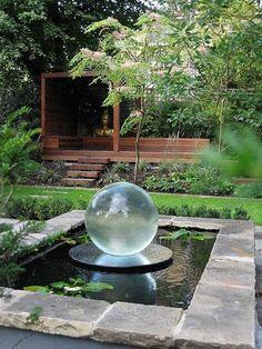 Beautiful modern backyard with water feature and fabulous outdoor lounging structure! - 40 Beautiful Garden Fountain Ideas