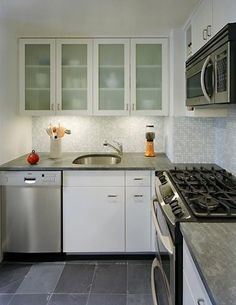 would consider cabinets with translucent glass. like the gray and white tile backsplash. cabinets are too press wood looking.