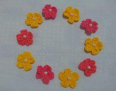 APLIQUE DE CROCHÊ FLORES <br> <br>Pequenas e delicadas flores coloridas confeccionadas em crochê com fio 100% de algodão, espessura média, com uma pérola bordada. <br> <br>Medida aproximada: 2,5 cm <br> <br>Ideal para customização de peças, tais como blusas, bolsas, peças em jeans, pacotes de presente, tags e cartões comemorativos. <br> <br>Também é uma opção para montagem de bijuterias, acrescentando um toque artesanal nas peças montadas com contas coloridas. <br> <br>Ótima sugestão para…