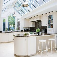 Kitchen extension with white kitchen island, white cabinetry and black granite worktops