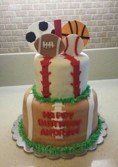 Andrews 1st birthday cake! Footballs, baseballs, basketball balls, soccer balls! The cutest little cake for the cutest little athlete! Bottom tier: marble cake with fresh strawberries and chocolate chips filling, top tier: vanilla cake with a vanilla filling.