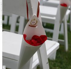 Monogrammed petal cones were tied to the backs of the aisle chairs at the ceremony. Red rose petals were scattered down the steps and onto the red aisle runner.
