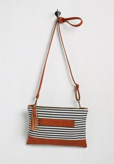 What do you think of when you see this casual purse? Its navy-and-white canvas stripes are sure to conjure up nautical concepts, while its chestnut brown, faux-leather accents - including a zipper tassel, a side handle, and an optional shoulder strap - inspire your train of thought to explore summery outfit options!