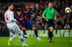 Neymar Santos Jr of FC Barcelona shoots the ball next to Mario Suarez of Club Atletico de Madrid during the Copa del Rey Quarter-Final First Leg match between FC Barcelona and Club Atletico de Madrid at Camp Nou on January 21, 2015 in Barcelona, Catalonia.