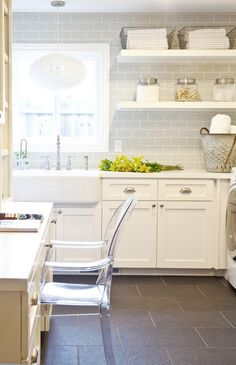 Perfect laundry room--open space, shelving, subway tiling, farmhouse sink, durable tile floors and a workspace to boot!