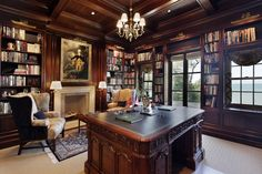 COOK ARCHITECTURAL Design Studio│This library and home office has a coffered ceiling, built-in bookshelves, a large stone mantle and fireplace, and dark wood detailing, as well as views to Lake Michigan as an inspiring workplace.
