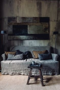 a wabi-sabi interior with a rough wooden wall, a wooden wall art of rough elements and a coarse textile sofa - DigsDigs