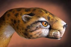 cheetah painted on a hand by Guido Daniele