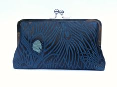 I made this stunning clutch bag using a shimmering teal and black peacock brocade fabric. With embroidered peacock eyes and feathers