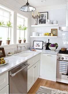 The kitchen is outfitted with a Thermador dishwasher and range. Sink fittings by Water­ works. Cabinets from Home Depot. Robert Ogden pen­dant, John Derian Company.
