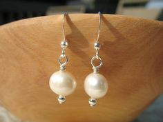 The timeless elegance of pearls makes these earrings perfect for any outfit!  Wear them to a wedding or while running your errands.  They make wonderful bridal gifts too!  The pearls measure about 1cm across and the earrings hang about 1 1/4inch long. $20.00