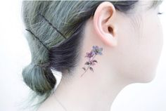 Colorful behind-the-ear flower tattoo by Tattooist Banul