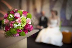 Wedding bouquet on table with couple in background -