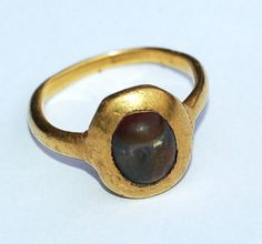 A 15th century high-carat gold amuletic ring set with a fossilized 'toadstone'. From the 14th century rings were set with 'toadstones' for their magical and protective qualities. According to folklore the toadstone had to be taken from an old toad that was still alive. This could be done by placing the toad on a piece of red cloth that would cause it to cast out its stone. There are a number of examples of toadstone rings in the British Musem, some contain fossilized ray-finned fish teeth…
