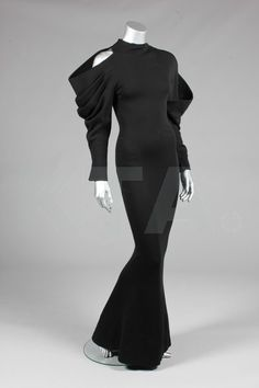 A Claude Montana black jersey evening gown, model 444, 1985, gold on white label, with one rounded curving shoulder and sleeve, the other with exposed shoulder and draped pleats, curving waist seam, long narrow skirt that slightly flares at the hem, bust 82cm,32in