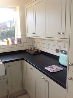 Howdens Greenwich Shaker Grey kitchen. Corian worktop in Deep Night Sky. Smeg toaster in pastel green.