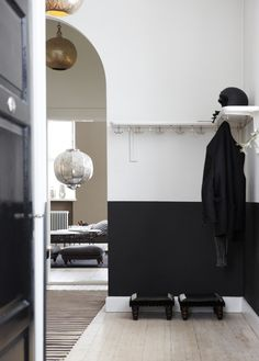This is just so lovely. The white pine floor, the coat rack, the matt black paint and the shiny black door.