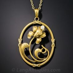 A sinuous Art Nouveau flavored orchid sprouts a natural freshwater pearl in this arty flower pendant, rendered in light but sturdy 10K gold during the first or second decade of the twentieth century. 1 5/8 inch by 1 inch, with 18 inch 9ct. chain.