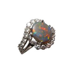 A quality Opal ring with an oval Black Opal and 2 mm bright white diamonds. A beautiful natural Opal ring to wear on any occasion or as an engagement ring.